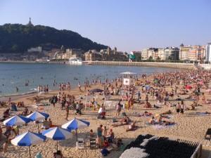 Tourists and locals relax in the summer sun on La Concha Beach, San Sebastian, Spain